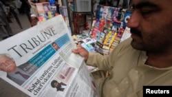 Một người đàn ông đọc tin về cái chết của thủ lĩnh Taliban Mullah Akhtar Mansour tại một sạp báo ở Peshawar, Pakistan, ngày 23 tháng 5 năm 2016.