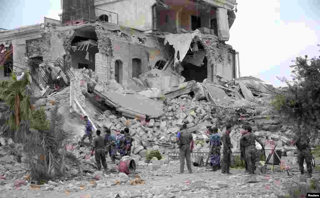 Forces loyal to President Bashar al-Assad stand on debris at a hotel used by al-Assad's forces, in historic Aleppo May 8, 2014.