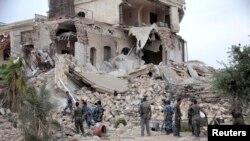 Halep'te bombalanan tarihi otelin enkazı önünde bekleyen Suriye askerleri