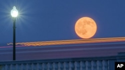 In this 2014 file photo, traffic streaks by the supermoon as it rises behind the Memorial Bridge in Washington, Saturday, July 12, 2014. (AP Photo/J. David Ake)