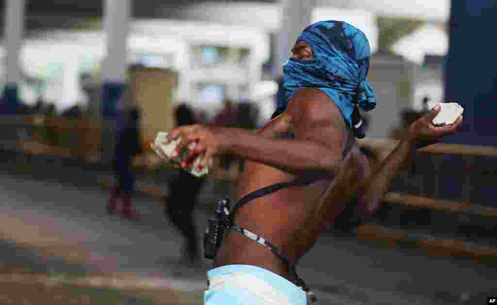 A demonstrator throws rocks at police outside the central train station, during protest against the increase on bus fares in Rio de Janeiro, Feb. 6, 2014.