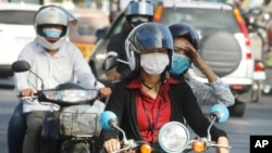 Cambodians wear masks to avoid the contact of coronavirus in Phnom Penh, Cambodia, Tuesday, Jan. 28, 2020. (AP Photo/Heng Sinith