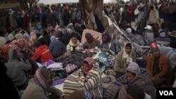 Para pekerja migran yang ingin meninggalkan Libya ini menunggu bis yang akan mengangkut mereka ke perbatasan dengan Tunisia, Kamis (10/3).