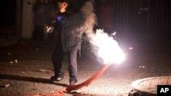 중국 베이징에서 한 남성이 담뱃불로 폭죽에 불을 붙이고 있다. (자료사진)