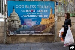 A woman walks past a poster praising U.S. President Donald Trump's recognition of Jerusalem as Israel's capital, in Jerusalem, Dec. 7, 2017.