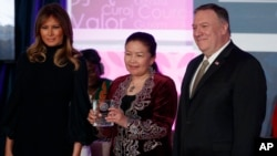 Sayragul Sauytbay, of China nominated by Kazakhstan, receives her award from first lady Melania Trump and Secretary of State Mike Pompeo during the 2020 International Women of Courage Awards Ceremony at the State Department in Washington Feb. 4, 2020. (AP Photo/Carolyn Kaster)