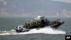 FILE - South Korean navy sailors in a speed boat patrol around South Korea's western Yeonpyong Island after finishing their exercise, near the disputed sea border with North Korea, February 20, 2012.