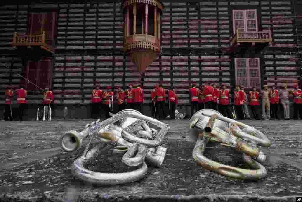 Anggota band polisi Jammu dan Kashmir berlindung dari hujan di sebuah kuil dan terompet diletakkan di tanah di Srinagar, kawasan India yang dikuasai oleh Kashmir.