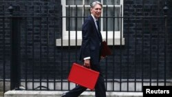 FILE - Britain's Chancellor of the Exchequer Phillip Hammond arrives in Downing Street in London, Britain, Sept. 7, 2016.