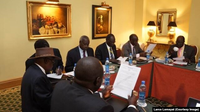 FILE - Negotiators at South Sudan peace talks in Addis Ababa review a draft cessation of hostilities agreement, Jan. 13, 2014.