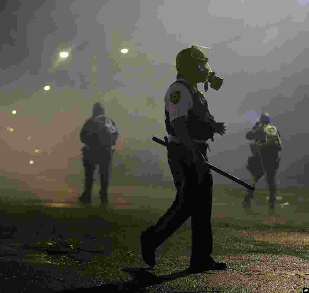 Law enforcement officers wait to advance, Aug. 17, 2014, after firing tear gas to disperse a crowd in Ferguson.