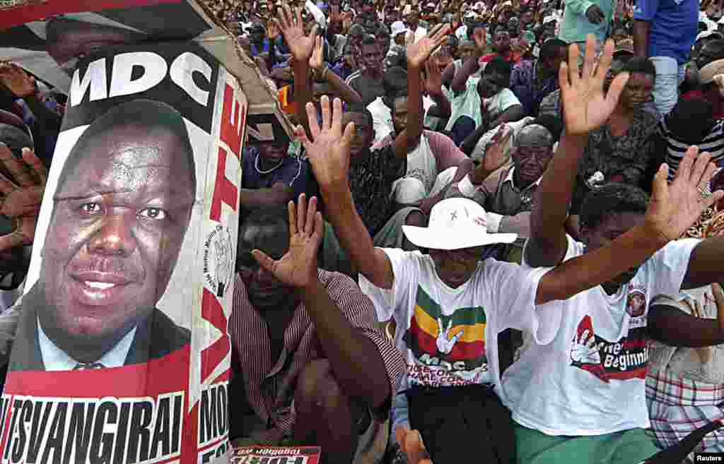 Supporters of the opposition Movement For Democratic Change (MDC) raise their hands as they cheer their leader Morgan Tsvangirai during a rally in Harare January 20, 2008.