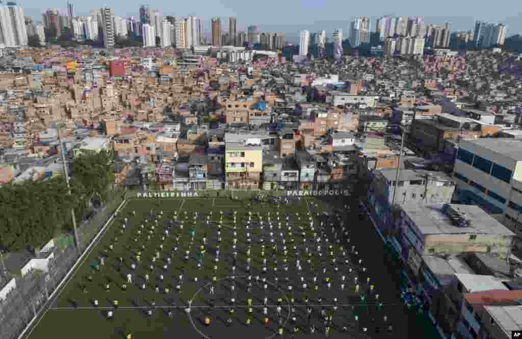 ប្រជាជនក្នុងតំបន់អនាធិបតេយ្យ Paraisopolis ចូលរួមក្នុងកម្មវិធីមួយនៅទីលានលែងទាត់បាល់ក្នុងទីក្រុង Sao Paulo ប្រទេសប្រេស៊ីល។