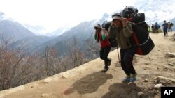 FILE - Nepalese porters carry heavy loads for climbers on their way to Everest Base Camp at Kyangjuma, Nepal in this April 7, 2015, photo.