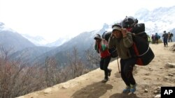 Nepalese porters carry heavy loads for climbers on their way to Everest Base Camp at Kyangjuma, Nepal in this April 7, 2015 photo.