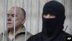 Olexiy Pukach, left, in a defendant's cage on the final day of his trial in Kiev, Ukraine, Jan. 29, 2013.