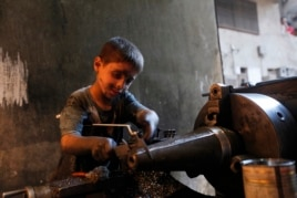 Issa, 10 years old, measures a mortar shell on a machine in a weapons factory of the Free Syrian Army in Aleppo, September 7, 2013. Issa works with his father in the factory for ten hours every day except on Fridays.
