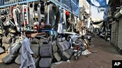 .بدھ کو کراچی کی کباڑی مارکیٹ میں بند دکانوں کے سامنے سے ایک شخص گزر رہا ہے۔