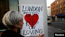 Une femme pose une affiche sur le London Bridge, après l'attaque à Londres, le 4 juin 2017.