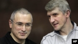 Mikhail Khodorkovsky (kiri) dan rekannya Platon Lebedev berbicara di pengadilan Moskow, Rusia (Foto: dok). Pengadilan Kota Moskow telah mengurangi hukuman bagi pemimpin oposisi dan mantan pengusaha minyak, Khodorkovsky, sehingga terbuka jalan baginya untuk bebas tahun 2014.