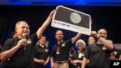 Investigadores de la sonda New Horizons celebran con la hija del descubridor de Plutón el récord mundial alcanzado por una estampilla sobre el planeta, que viaja con la nave.