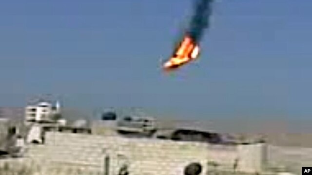 This citizen journalism image purports to show a Syrian military helicopter on fire and falling to the ground after it was apparently hit during fighting between government forces and rebels in Damascus, Aug 27, 2012. AP IS UNABLE TO INDEPENDENTLY VERIFY