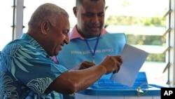 Penguasa militer Fiji Voreqe Bainimarama (kiri) memberikan suaranya pada pemilu September 2014 di Suva, Fiji. (AP/Pita Ligaiula)