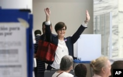 """Leah Schier throws up her arms after casting her ballot in Dallas, Nov. 8, 2016. """"I was so exited to cast my vote for a woman,"""" she said."""