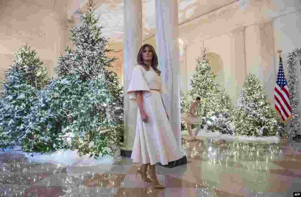 """美国第一夫人梅拉尼亚·川普在白宫前厅观看圣诞节的布置情况(2017年11月27号)。今年的布置由她主导,来自29个州,超过150名的义工,将白宫打扮成银白世界。今年的主题叫做""""悠久传统""""(Timed-Honored Tradition)。"""