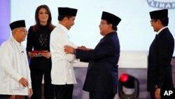 Para kandidat bersalaman seusai debat perdana hari Kamis malam (17/1) di Jakarta.
