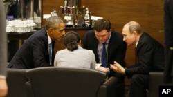 U.S. President Barack Obama, left, speaks with Russian President Vladimir Putin, right prior to the opening session of the G-20 summit in Antalya, Turkey, Nov. 15, 2015.