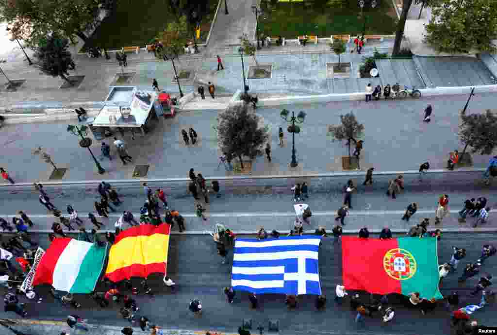 Protesters march through Syntagma square in Athens with flags of Italy, Spain, Greece and Portugal, November 14, 2012.