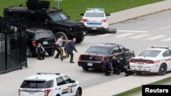 Police officers take cover near Parliament Hilll following a shooting incident in Ottawa, Canada.