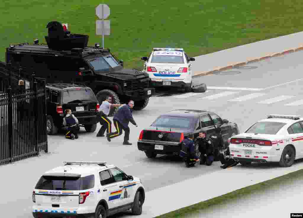 Police officers take cover near Parliament Hill after a shooting in Ottawa, Canada. A Canadian soldier was shot and killed at the National War Memorial in downtown Ottawa and a gunman was shot and killed in a nearby parliament building, media and witnesses reported.