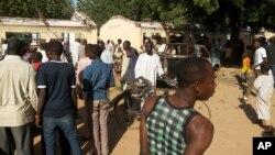 10일 나이지리아 포티스쿰시의 고등학교에서 폭탄테러가 발생한 가운데, 주민들이 테러 현장 주변에 모여있다.