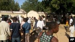 Une foule contemple le lieu d'un attentat à la bombe à l'école technique et scientifique publique de Potiskum, Nigeria, le 10 novembre 2014.