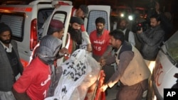 Pakistani volunteers carry the body of a militant killed during a crackdown by security forces in Quetta, Dec. 19, 2014.