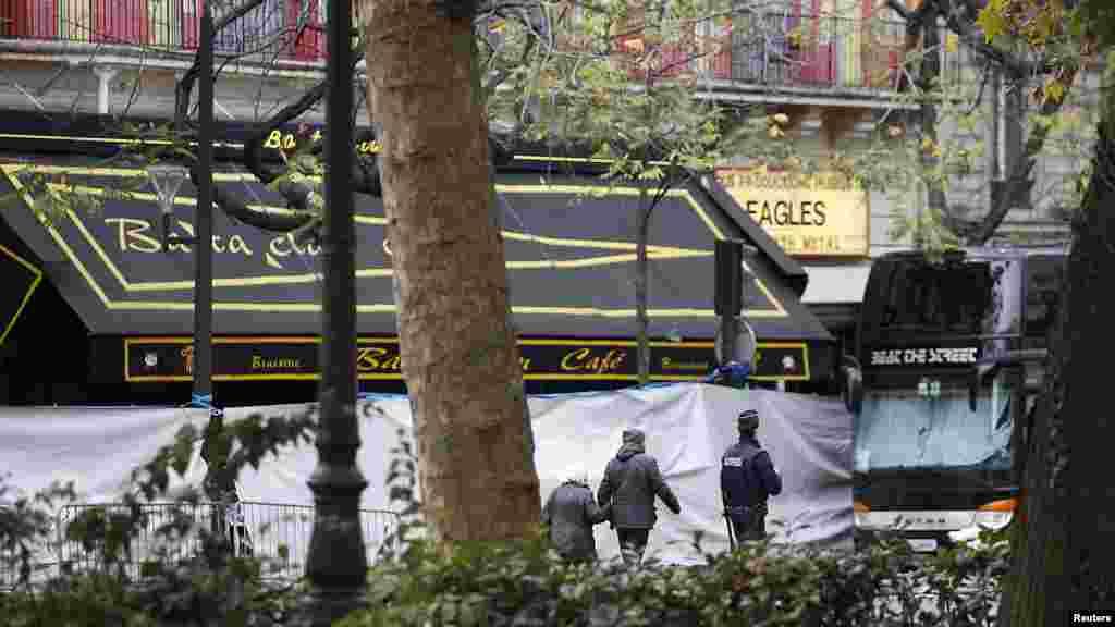 """یک روز پس از رشته حملات مرگبار در پاریس، رهگذران از مقابل کافه """"باتاکلان"""" و سالن کنسرت مجاورش که محل حادثه بود عبور می کنند."""