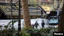 Warga berjalan melewati sebuah Cafe di dekat gedung konser Bataclan di Paris sehari setelah serangan maut (14/11). Serangan teror di Paris menimbulkan kerugian hingga dua milyar euro atau sekitar 2,12 milyar dolar pada perekonomian Perancis yang sudah stagnan.