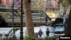 Orang-orang berjalan melewati Bataclan Cafe dan gedung konser sehari setelah serangkaian serangan maut di Paris, 14 November 2015.