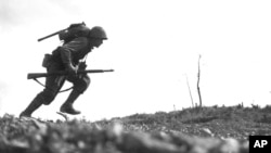 Binh sĩ Paul Ison của Sư Đoàn 6 Thủy Quân Lục Chiến Mỹ băng qua làn đạn súng máy của lực lượng Nhật Bản trên đảo Okinawa, ngày 10 tháng 5, 1945.