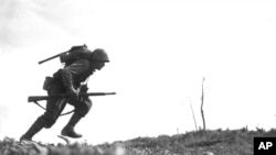 Pfc. Paul Ison, a U.S. Marine runs through Japanese gunfire on Okinawa, May 10, 1945.