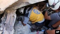 Esta foto provista por los Cascos Blancos de Defensa Civil sirios, que ha sido autenticada en base a su contenido y otros informes de AP, muestra a trabajadores de defensa civil sirios retirando un cuerpo de los escombros en el lugar de una explosión que derrumbó un edificio de cinco pisos en el pueblo de Sarmada, cerca de la frontera turca, en el norte de Siria, domingo, 12 de agosto de 2018.