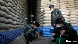 FILE - Soldiers check rice stocks at a warehouse in Ayutthaya province, north of Bangkok, Thailand, July 3, 2014. Thailand plans to sell the remaining 11.4 million tons of rice in government stockpiles within two months.