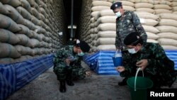 FILE - Soldiers check rice stocks at a warehouse in Ayutthaya province, north of Bangkok, Thailand.