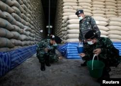 FILE - Soldiers check rice stocks at a warehouse in Ayutthaya province, north of Bangkok, Thailand, July 3, 2014.