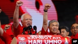 Malaysian Prime Minister and President of Malaysia's ruling party United Malays National Organization's (UMNO) Najib Razak (left) and Deputy Prime Minister Ahmad Zahid Hamidi chant a slogan during a celebration of party's 71st anniversary in Kuala Lumpur,