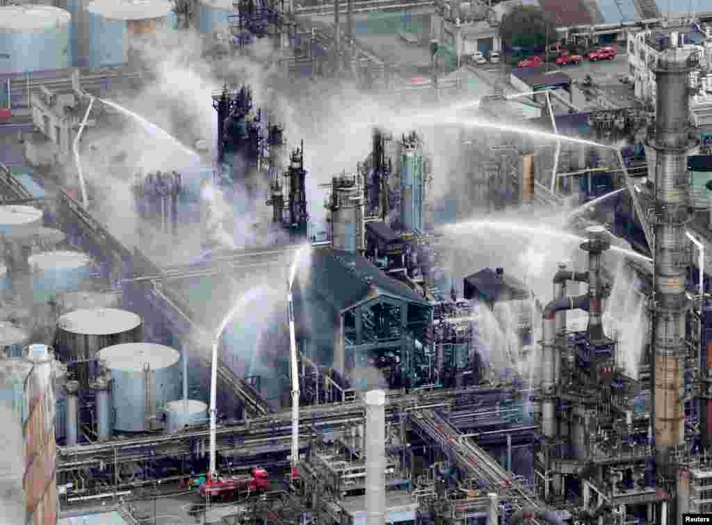Fire trucks extinguish a fire at a TonenGeneral Sekiyu KK's oil refinery in Arida, Wakayama Prefecture, western Japan, in this photo taken by Kyodo.