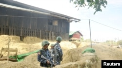 Myanmar border guard police stand guard at Goke Pi outpost in Buthidaung during a government organized media tour in Rakhine