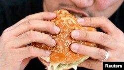 Seorang pria sedang melahap sepotong hamburger di Hollywood, California, 3 Oktober 2007. (Foto:Dok)